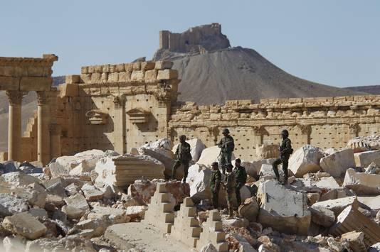Syrische soldaten houden de wacht tussen de puinhopen van Palmyra, een van de reisdoelen van Clio.