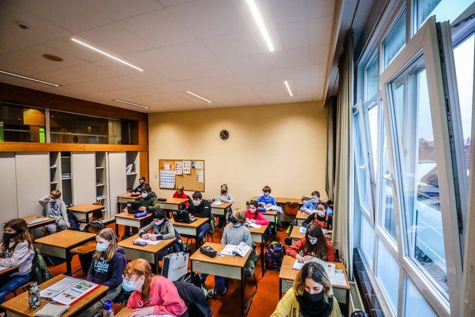 Leerlingen in de Middenschool volgen les terwijl de ramen openstaan.