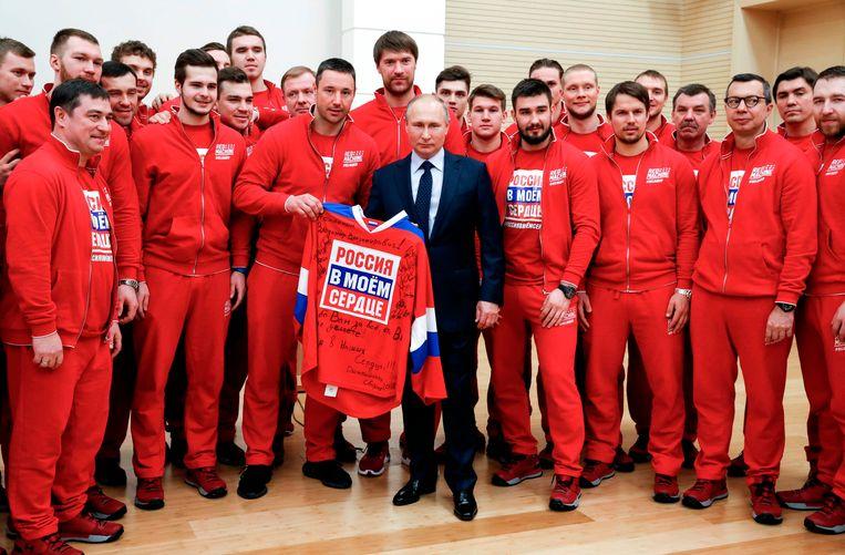 Russische ijshockeyers poseren met president Poetin. De ploeg werd vorig jaar olympisch kampioen. Vanwege de schorsing speelden ze onder de neutrale naam 'olympic athletes from Russia'. Beeld AFP