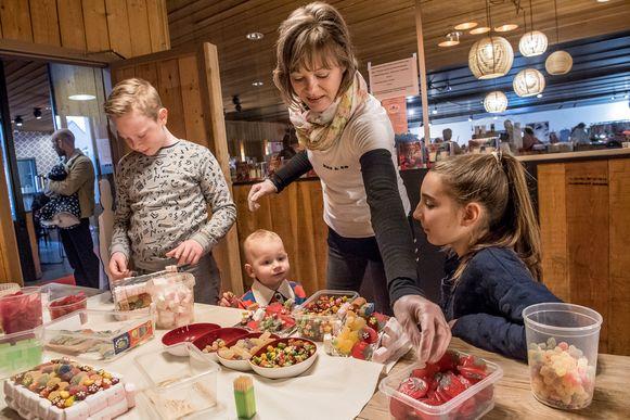 Mede-organisatrice Cindy Wielfaert maakt snoeptaarten samen met Stan, Janne en Stella.