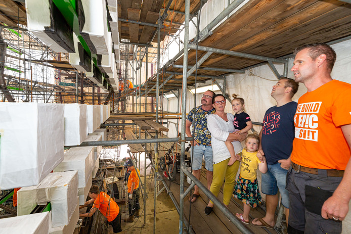 Luke Henselmans (oranje T-shirt) van de Venomenaal geeft bezoekers uitleg over de bouw van de praalwagen.