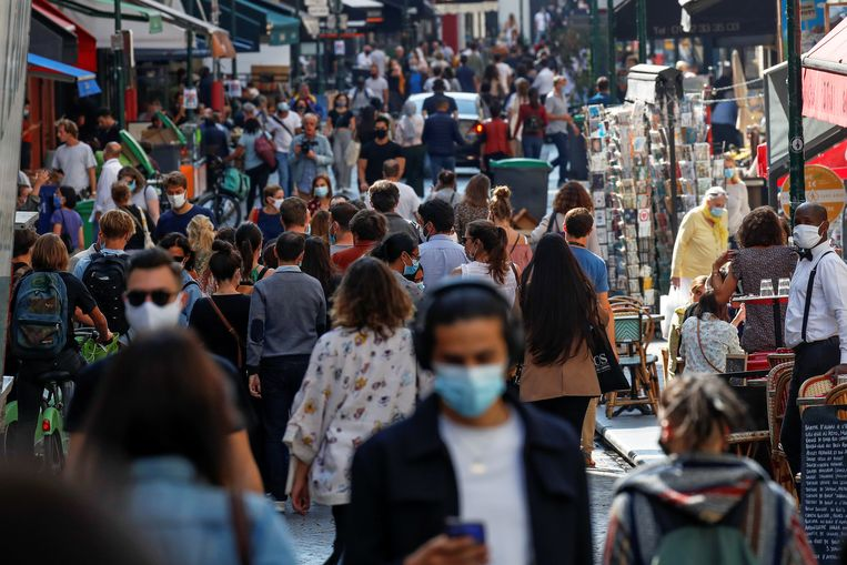 Passers-by wear masks on a busy Paris street.