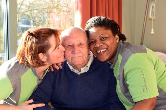 Sofie Cottem (l) en Essi Hounkpatti feliciteren Albert Delaere uitbundig voor zijn 100ste verjaardag .