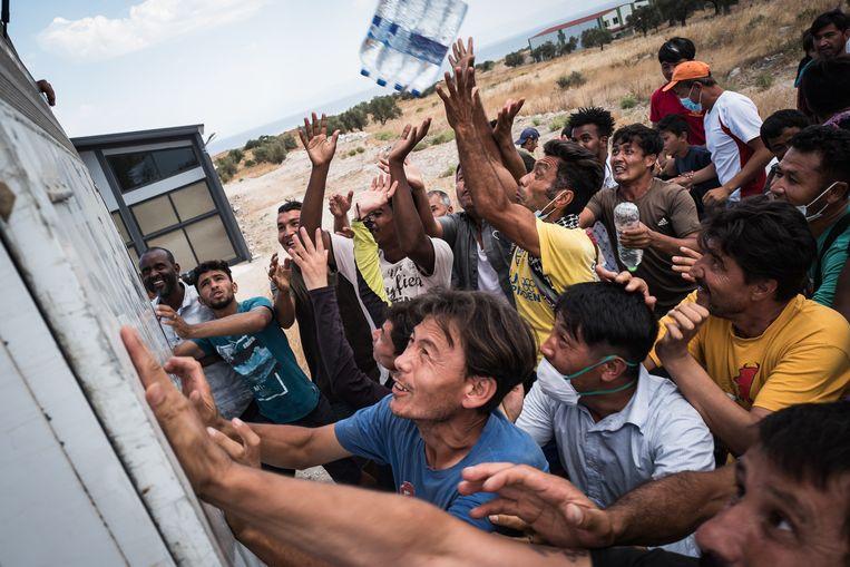 Vluchtelingen op Lesbos proberen een flesje water te bemachtigen. Beeld Nicola Zolin