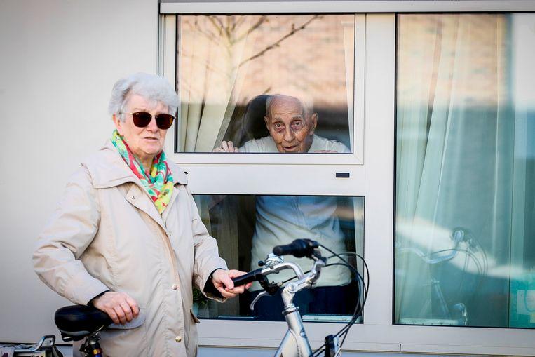 Een vrouw begroet haar echtgenoot door het raam van een rusthuis. Archiefbeeld.