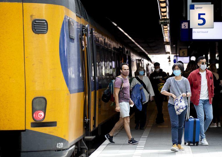 Reizigers met mondkapjes op Den Haag Centraal Station. Beeld ANP