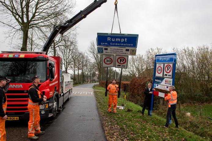 Rumpt is niet langer gemeente Geldermalsen. Burgemeester Harry Keereweer (tweede van rechts) hielp deze week een handje bij het verwisselen van een kombord bij het dorp.