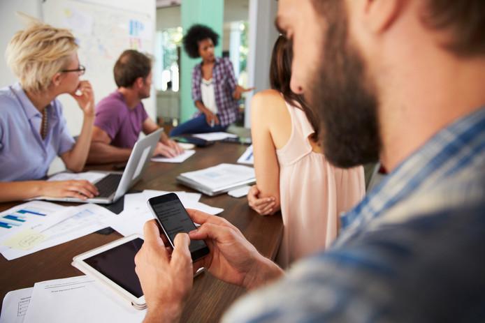 Met stip op 1 staan collega's die hun telefoon gebruiken tijdens vergaderingen of gesprekken.