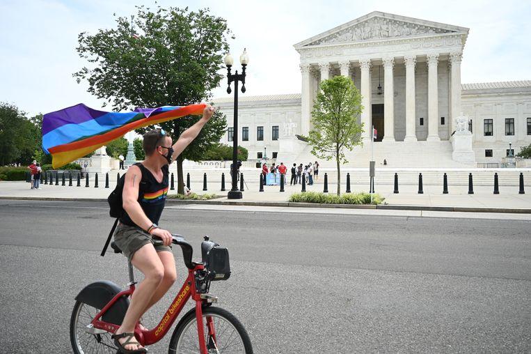 Een man zwaait op de fiets met een regenboogvlag voor het Amerikaanse Hooggerechtshof. Beeld AFP