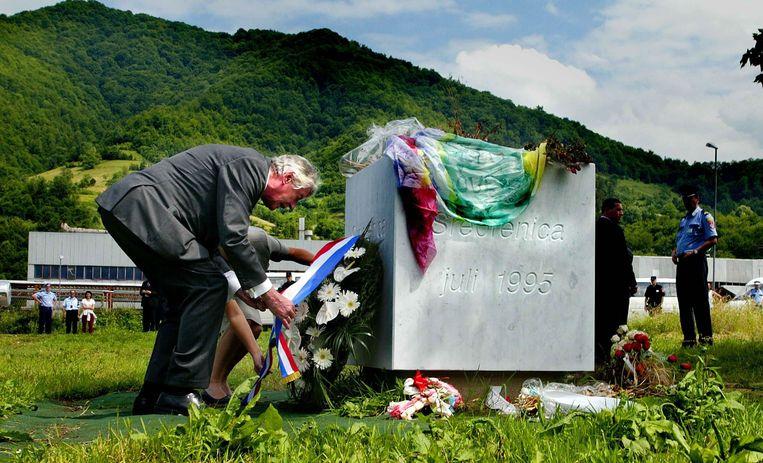 Voormalig premier Kok legt in 2002 op een veldje tegenover de compound van Dutchbat in Potocari een krans ter nagedachtenis aan de duizenden moslims die daar zijn vermoord. Beeld null