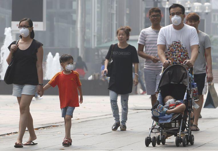 Mensen in Singapore met mondkapjes voor hun mond Beeld reuters