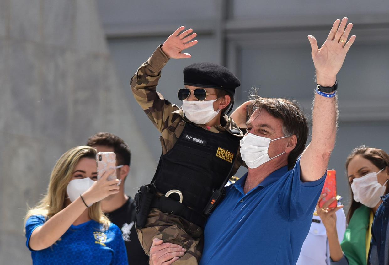De Braziliaanse president Bolsonaro neemt het zo nauw niet met de social distancing. Zondag verscheen hij voor een menigte supporters en nam hij zelfs een paar kinderen op de arm. Beeld AP