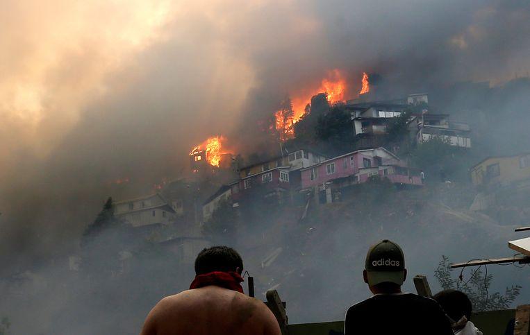 Mannen kijken toe terwijl de vlammenzee het ene na het andere huis verwoest in de Chileense kustplaats Valparaíso.