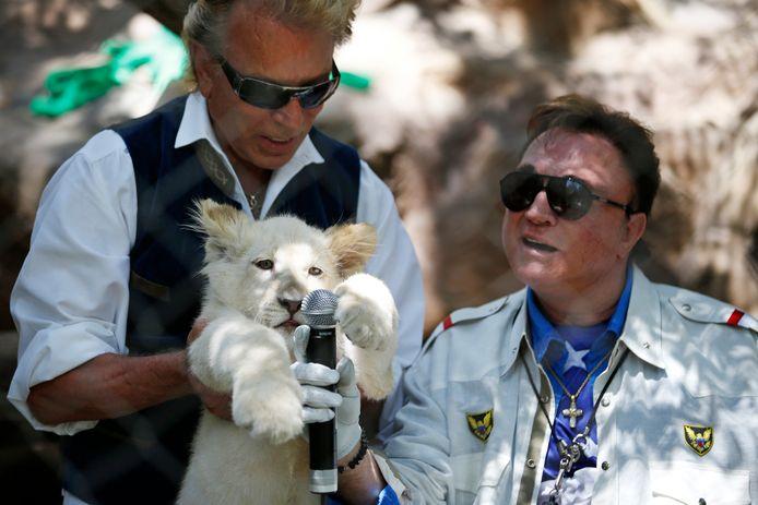 Siegfried Fischbacher houdt in 2014 een welp vast, naast Roy Horn.