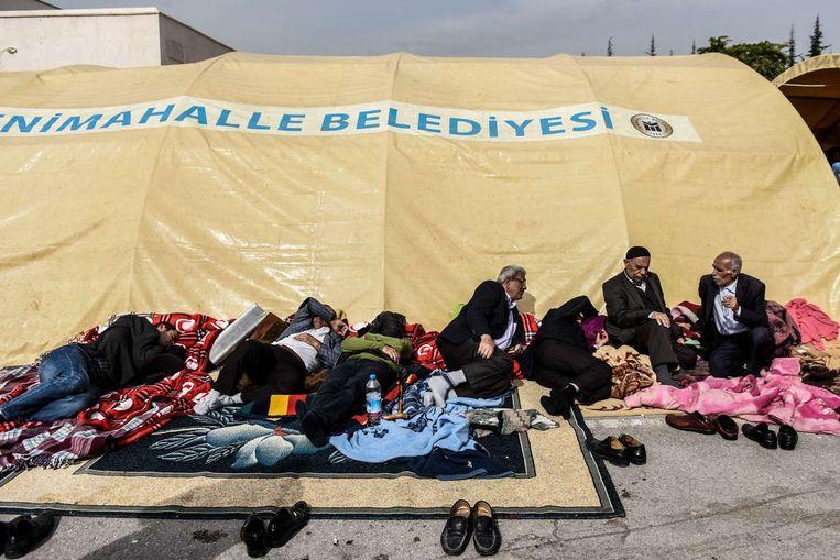 Nabestaanden wachten op nieuws bij een geïmproviseerd mortuarium. Beeld AFP