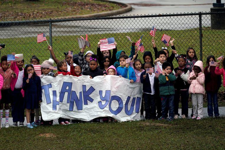 Kinderen zwaaien de overleden president uit met een groot spandoek met 'dank u' erop en Amerikaanse vlaggetjes.