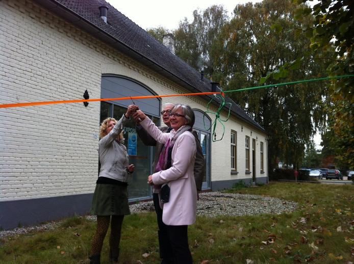 Myriam Simons (links), Fer van Campen en wethouder Annemieke van de Ven knippen een lint door om de verkoop te bezegelen.