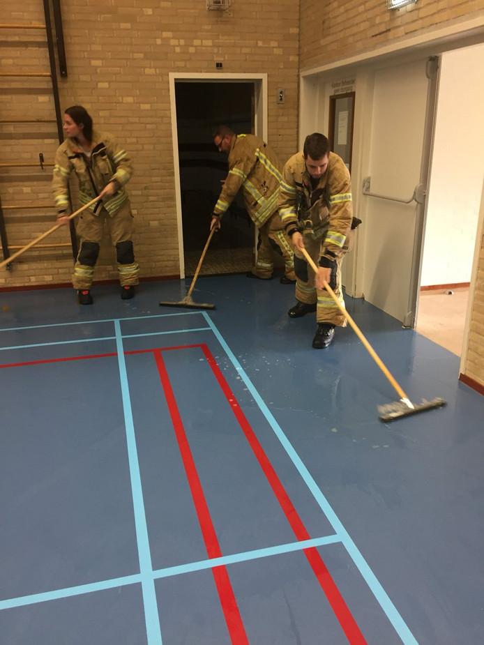Brandweerlieden maken de sporthal weer schoon.