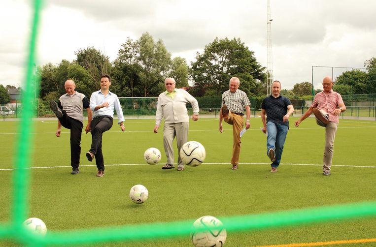 Bestuursleden van voetbalclub White Boys trappen met sportschepen Peter Buysrogge een balletje op het nieuwe kunstgrasterrein.