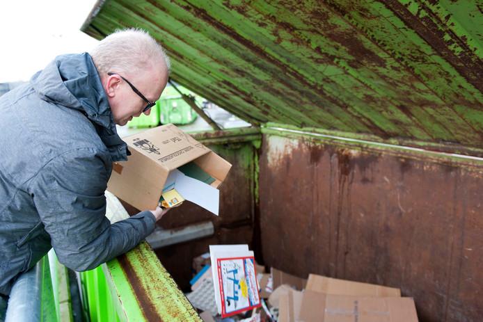 Een man gooit oud-papier in een papiercontainer in de milieustraat van Raalte.