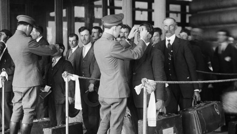 Immigranten worden gecontroleerd bij aankomst op Ellis Island net voor de kust bij New York. Beeld UIG via Getty Images