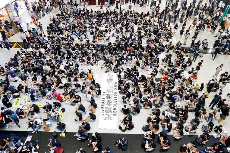 Demonstranten tegen de uitleveringswet op het vliegveld van Hongkong. Volgens Beijing zijn de protesten door 'buitenlandse krachten' uitgelokt.  Beeld REUTERS