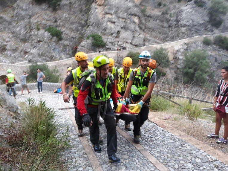 Een gewonde wordt weggedragen. De slachtoffers bevonden zich in een kloof in Calabrië. Daar deed zware regenval het water in een riviertje stijgen.