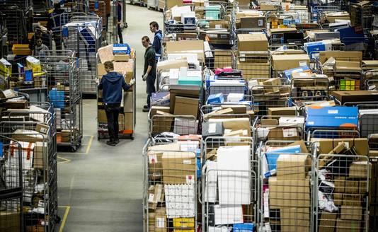 Medewerkers van PostNL sorteren pakketjes in het pakkettensorteercentrum