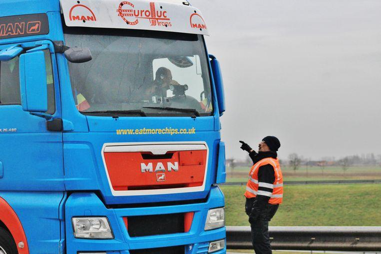Een politieman legt een vrachtwagenchauffeur uit dat hij niet mag doorrijden richting Frankrijk.