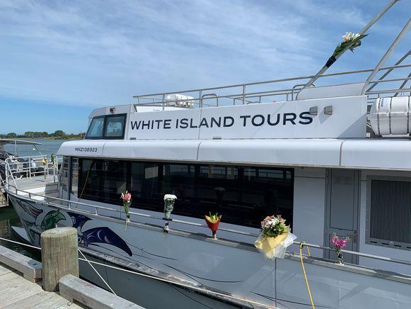 Bloemen zijn bevestigd aan een bootje van White Island Tours, een van de bedrijfjes die de rondleidingen op White Island verzorgde.