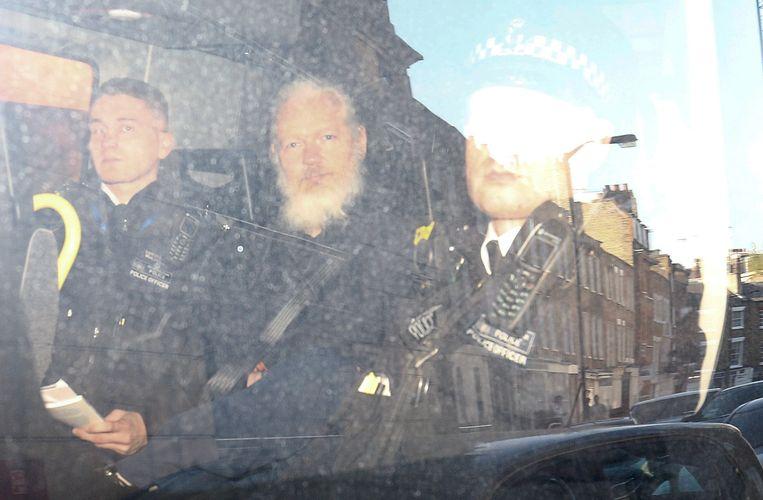 Wikileaks-stichter Julian Assange verlaat onder politiebegeleiding de rechtbank in Londen. Beeld REUTERS