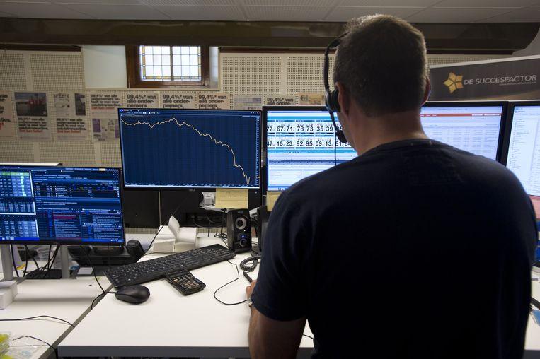 Een grafiek op het computerscherm van een beursmedewerker toont de daling van de AEX-index. Beeld anp