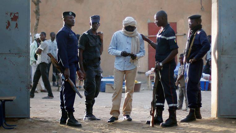 Een Malinese politieman controleert de stemkaart van een man Beeld AP