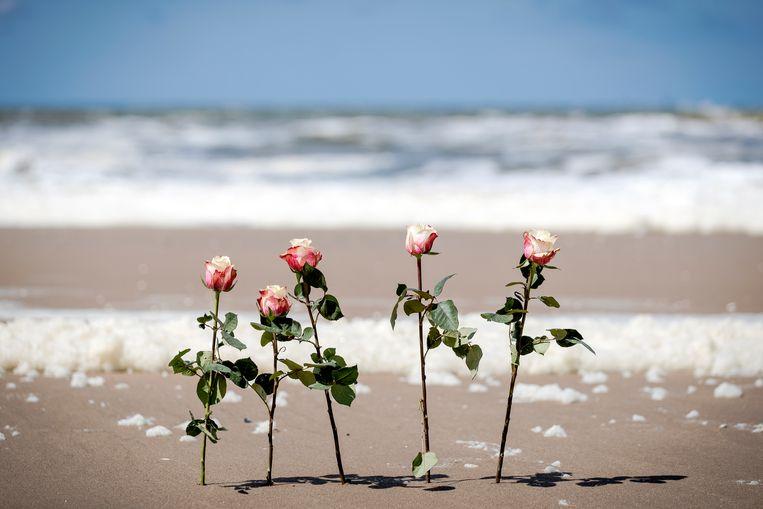 Bloemen tussen het schuim op het strand van Scheveningen.  Beeld ANP