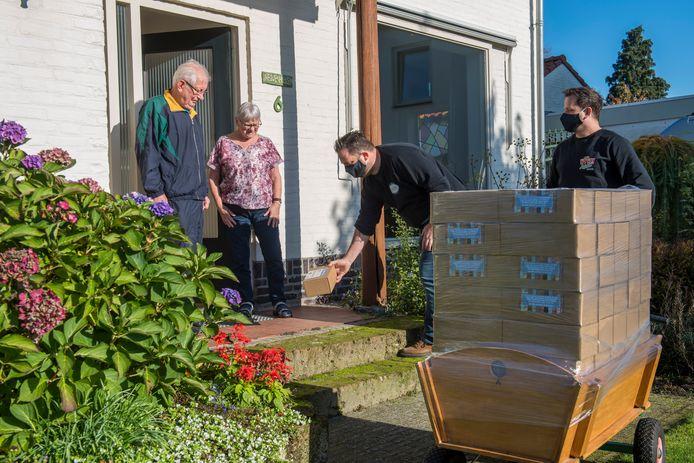 Horecaondernemer Willem Neutkens deelt samen met compagnon Bart Theuws (van Willy Nachos) pakketjes met nachos, dipsaus en pastasaus uit aan Noud en Martha van de Nieuwehuyzen.