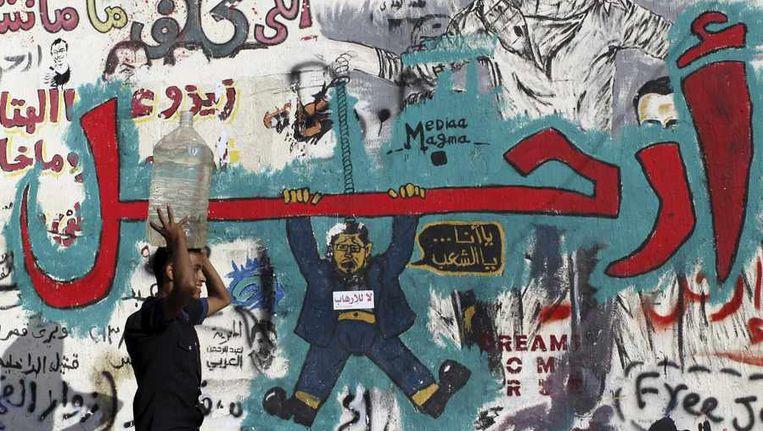 Een Egyptenaar loopt langs een wand vol anti-Morsi-graffiti. Beeld reuters