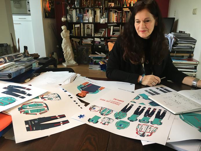 Karin Slegers temidden van ontwerpen voor de nieuwe kleding van 6000 ambulanceverpleegkundigen.