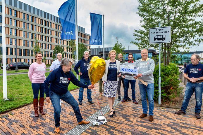 Peter van der Velden en Christianne Lennards nemen een cheque in ontvangst van de initiatiefnemers van de actie voor het Amphia-personeel.