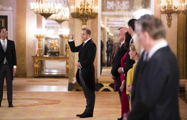 De eed - De dag begon voor nieuwe ministers en staatssecretarissen in de Grote Balzaal van Paleis Noordeinde. Eerst stelde premier Mark Rutte hen voor aan Koning Willem-Alexander, waarna zij de eed of belofte aflegden. Alle ministers van CDA en ChristenUnie kozen voor de eed en zwoeren aan God, net als D66'er Sigrid Kaag (ontwikkelingssamenwerking en buitenlandse handel) en VVD'er Bruno Bruins (medische zorg). Kaag was de enige D66'er die voor de religieuze variant koos. Bij de staatssecretarissen kozen ook de VVD'ers Mark Harbers (immigratie) en Barbara Visser (defensie) voor de eed. Premier Rutte kreeg geen ontslag, hij behoudt zijn functie en hoefde derhalve niet beëdigd te worden. Beeld ANP