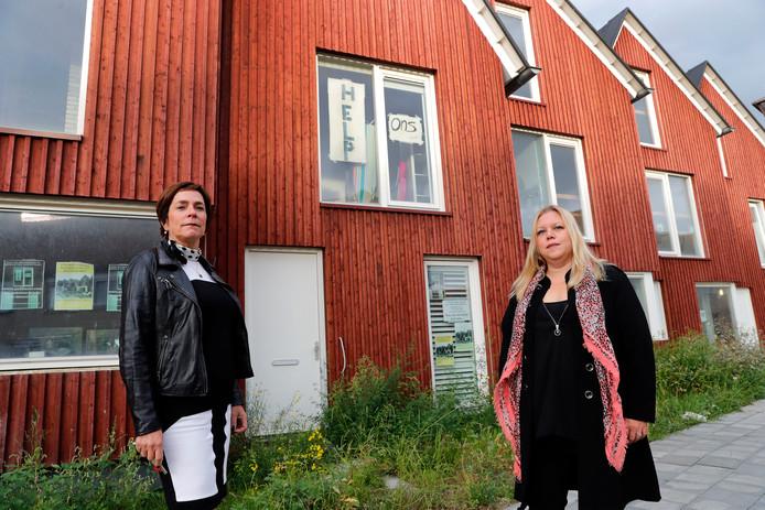 Dineke van Ommen en Nancy Snijders bij hun onbewoonbaar verklaarde huizen.