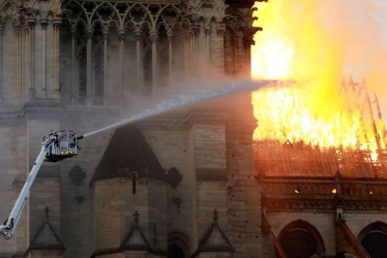 Een brandweerman bestrijdt de vlammen die uit de Notre Dame omhoog komen. Beeld Getty Images