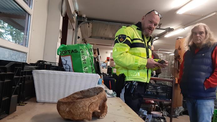 De wijkagent informeert bij een medewerker van Kringloop Twello naar de aangetroffen menselijke schedel.