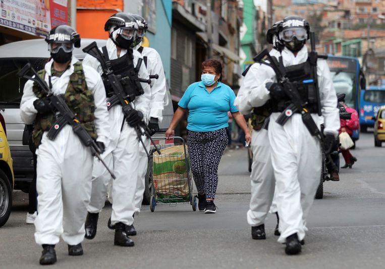 Soldaten in een beschermend pak patroulleren in een wijk in Bogota.