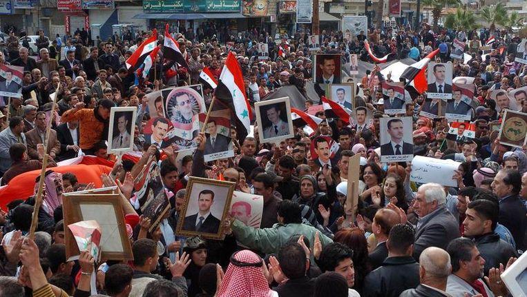 Mensen gaan de straat op om steun te betuigen aan de Syrische president Assad, 13 november 2011. Beeld afp