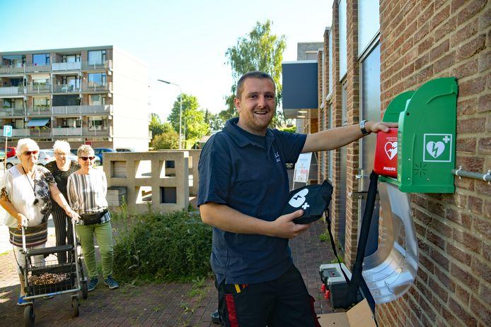 Voor het oog van een aantal betrokken buurtbewoners hangt Tom Verdurmen de AED op die hij in korte tijd voor de Terneuzense wijk Katspolder wist te regelen.