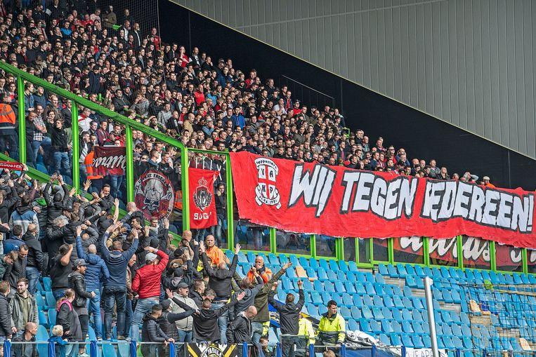 Vitesse fans treiteren de FC Twente fans die achter de groene omheining staan Beeld null
