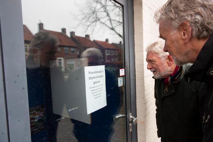 Matthie Kroezen (links) en Hans Strootman van de dorpsraad lezen de mededeling nog maar eens: de pinautomaat is weg.