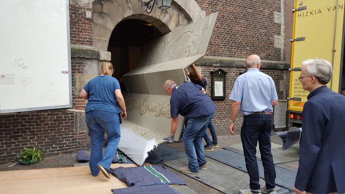 Het moment dat een van de luiken in Amsterdam door de deur van de Westerkerk naar buiten gaat.