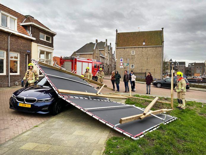 Aan de Noorddijk in Maassluis is zondagmiddag tijdens de storm een reclamebord op een auto gewaaid.