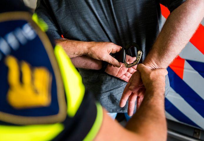 Een arrestant wordt geboeid en in een politiewagen gezet. Foto ter ilustratie.